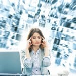 Stress - kvinde foran computer har tusinde tanker i hovedet