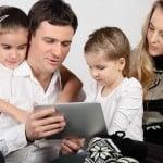 Ung familie med to børn ser på en iPad tablet