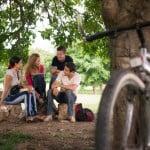 En gruppe unge mennesker hygger i parken - cykel parkeret op ad et træ